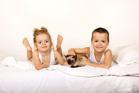 Kids in pajamas playing with their kitten on the bed Stock Photo