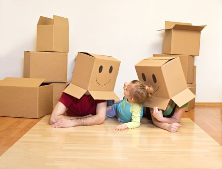 Family having fun laying on the floor of their new home with lots of cardboard boxes photo