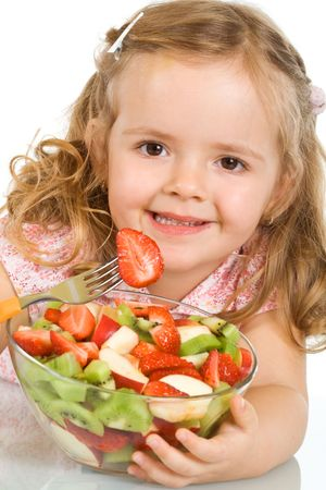 Happy little girl with a large bowl of healthy fresh fruit salad - closeup, isolated photo