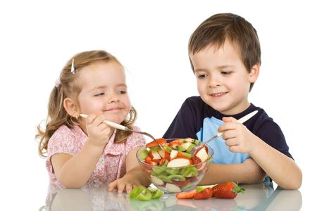 Happy smiling kids eating fruit salad - isolated photo