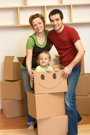 Happy family unpacking in their new home - lots of cardboard boxes all around