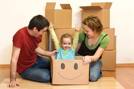 Happy family on the floor of their new home with lots of cardboard boxes, unpacking photo
