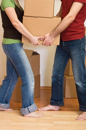 unpacking: Man and woman, carry cardboard boxes - moving into a new home concept Stock Photo