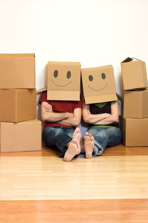 family moving house: Happy couple in their new home having fun - moving concept