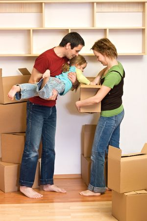 Family unpacking from lots of cardboard boxes in their new home - moving concept photo