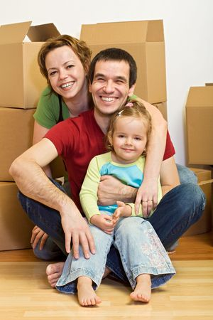 Happy family sitting on the floor in their new home with lots of boxes - moving concept photo