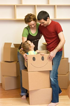 unpacking: Happy family unpacking in their new home with lots of cardboard boxes Stock Photo