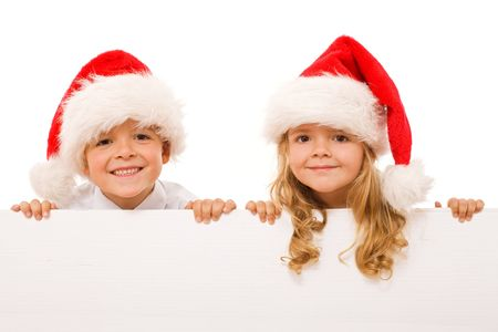 Happy kids with santa hats and white cardboard - isolated christmas message, closeup Stock Photo - 5743706