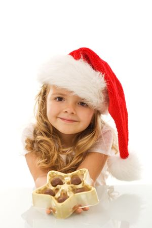 Happy little girl with santa hat holding christmas star shaped box with chocolate - isolated photo