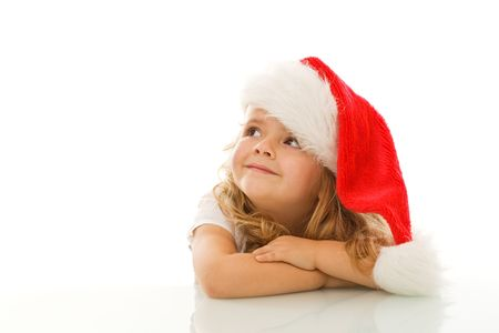 Happy little girl waiting for christmas wearing a santa hat - isolated photo