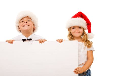 Happy kids with santa hats and white cardboard - isolated christmas message photo