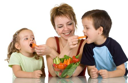 children eating: Woman feeding kids with fresh vegetables - the joy of eating healthy food