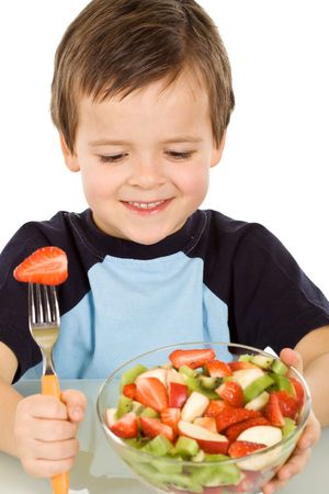 Healthy boy about to eat a large bowl of fresh fruit salad - isolated photo