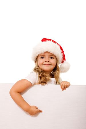 Smiling happy christmas hat girl pointing to white banner - isolated photo