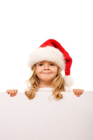 Little girl with santa hat smiling behind a cardboard banner - isolated photo