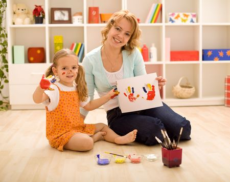 Woman and little girl painting hand and making prints- focus on the girl face photo