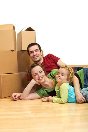 The first day in our new home - young family laying on the floor with cardboard boxes, isolated photo