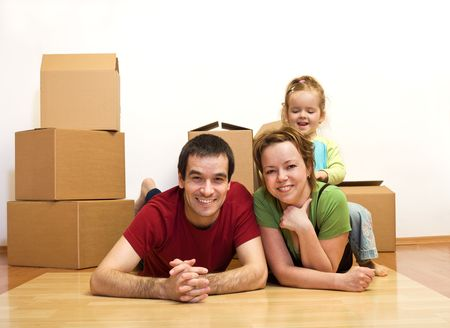 Finally in our new home - young family laying on the floor among cardboard boxes, moving concept photo