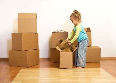 unpacking: Excited little girl with cardboard boxes, unpacking in her new home