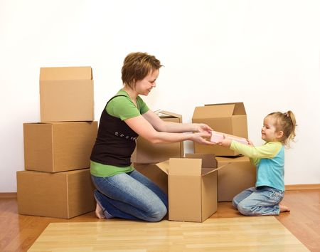 unpacking: Woman and little girl in a new home unpacking from cardboard boxes