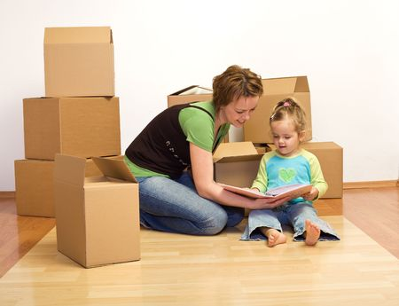 unpacking: Unpacking in our new home - woman and little girl with cardboard boxes sitting on the floor