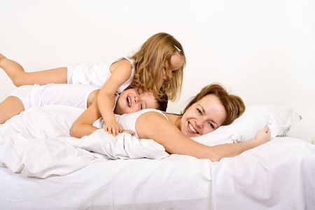 Happy morning - woman and kids in bed on a carefree morning photo