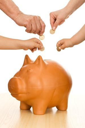 Hands of different generations putting coins in piggy bank - saving money concept Stock Photo - 6250650