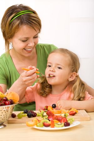 Eating healthy fruits is delicious and fun - woman and little girl enjoying a fresh dessert photo