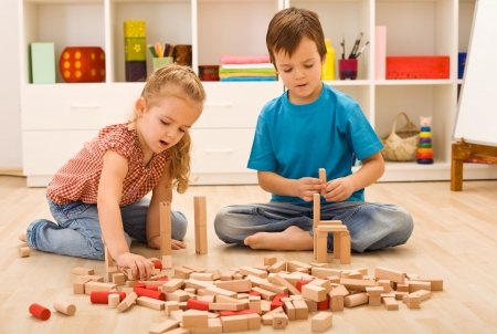 tower block: Little builders - boy and girl playing with wooden blocks