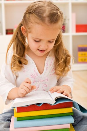 Little girl preparing for school - sitting with a stack of books in her lap Stock Photo - 6318298