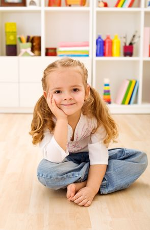 little girl sitting: Happy little girl sitting in her room at home
