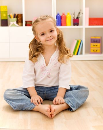 little girl sitting: Happy healthy little girl sitting on the floor in her room smiling joyfully Stock Photo