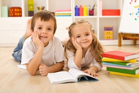 Happy kids with colorful books laying on the floor in their home photo