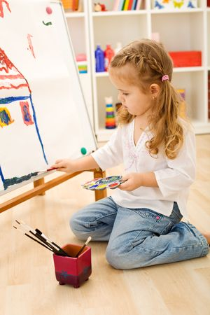 focused: Little artist girl painting a house focused on the work Stock Photo