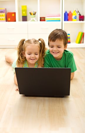 Kids with laptop laying on the floor at home photo