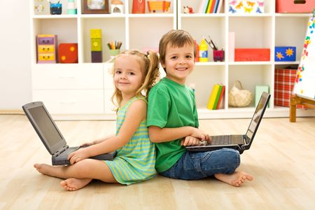 Happy kids with laptops sitting on the floor in their room photo