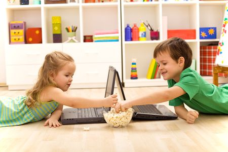 Kids with laptops eating popcorn in their room photo