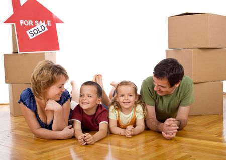 Happy family with two kids in their new home laying on the floor among cardboard boxes photo