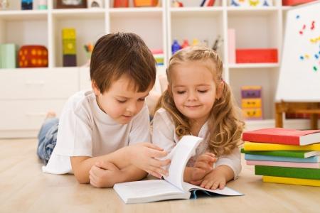 School jongen die op de vloer het onderwijs en het tonen van haar zus hoe om te lezen