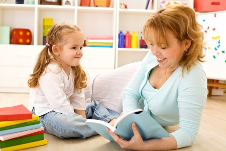 child reading: Little girl having fun with her mother reading stories on the floor