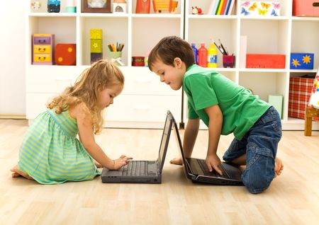 Kids playing on laptops - boy teaching little girl what key to press photo