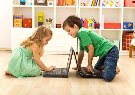 Kids playing on laptops - boy teaching little girl what key to press Stock Photo - 12477080