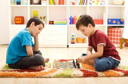 Permettez-moi de vous montrer un mouvement - enfants jouant aux échecs assis sur le sol dans leur chambre Banque d'images - 12476933