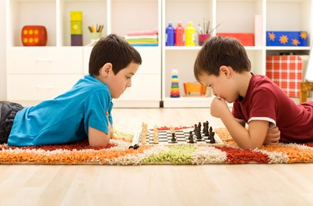 Serious kids playing chess laying on the floor in their room photo