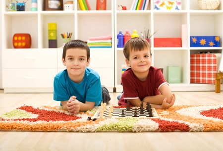 Young kids preparing to play chess laying on the floor at home photo
