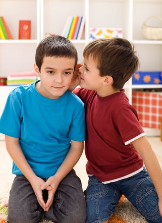 So buddy here is the plan - two kids whispering secrets photo