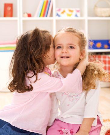 delightful: Little girls sharing a delightful secret