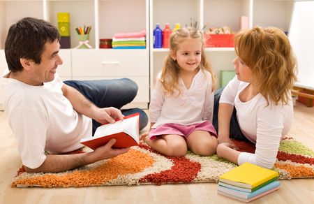 Happy family reading a story laying on the floor in the kids room photo