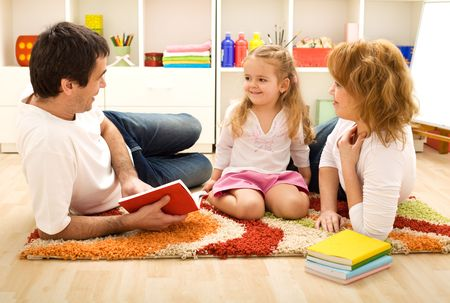 school work: Story time - happy family with a child reading a book laying on the floor Stock Photo