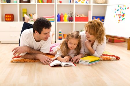 parents: Happy family laying on the floor reading in the kids room